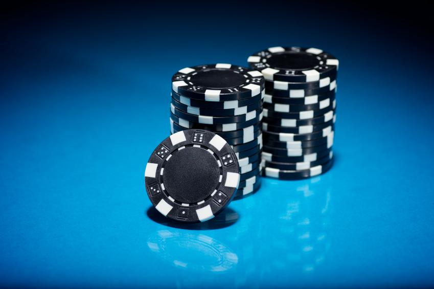 Black poker chips against a blue back ground